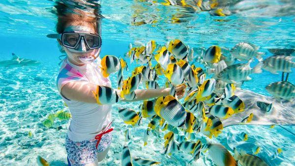 девушка кормит рыб